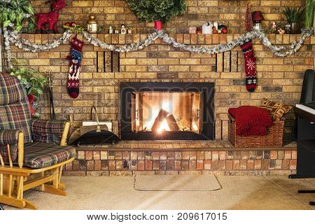 Roaring Fire In A Vinrage Brick Frieplace Decorated For Christmas, With Piano, Rocking Chair And Coz