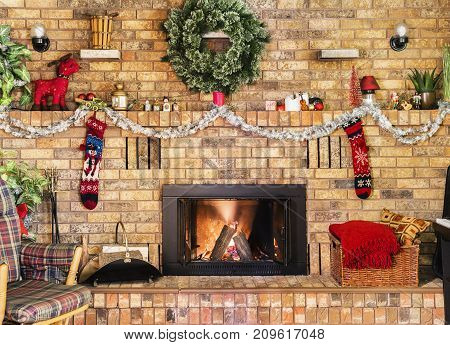 Cozy Fire In Brick Fireplace And Mantle Decorated For Christmas