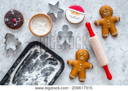 Cook gingerbread for new year 2018. Gingerbread man, rolling pin, flour on stone background top view. mock up