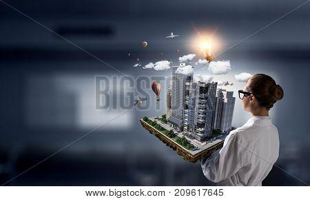 Woman presenting construction model. Mixed media