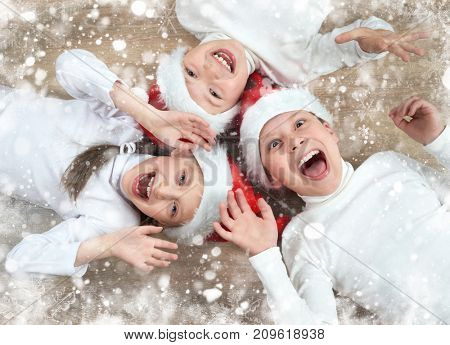 happy child lying together on wooden background, dressed in christmas Santa hat and having fun, winter holiday concept, snow decoration