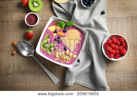 Bowl with acai smoothie on wooden background