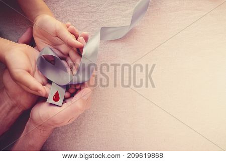 Adult and child hands holding grey ribbon World Diabetes day
