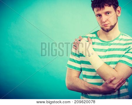 Pain and injury concept. Young man holds bandaged hand. Injured part of body. Medicine and healthcare.