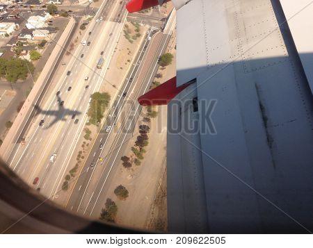 Hey stark shadow tags along a landing 747 as it lands in a metropolitan international airport.