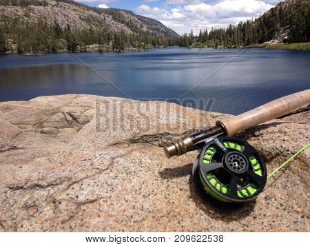 An Angler rests a flyrod upon a granite boulder next to a calm, serene, high elevation, alpine lake .