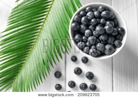 Bowl with fresh acai berries and palm leaf on wooden table