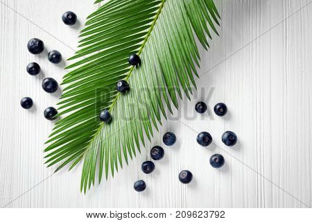 Fresh acai berries and palm leaf on wooden background