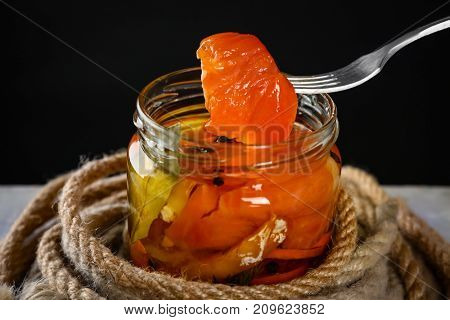 Fork and jar with delicious marinated salmon on black background