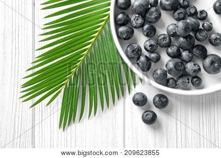 Plate with fresh acai berries and palm leaf on wooden table