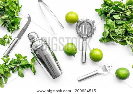 Make mojito cocktail with lime and peppermint in shaker. White background top view.