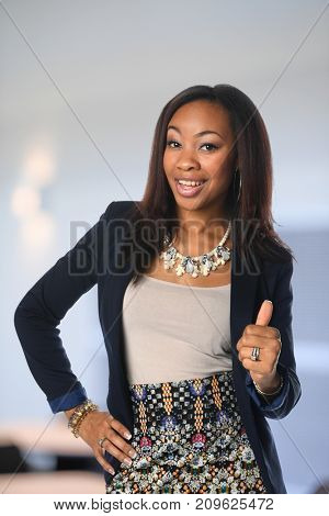 Young African American businesswoman showing the thumbs up inside office building