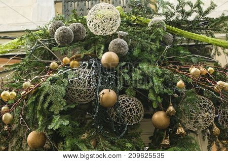 Decoration made from fir branches and golden balls on the wall of a shop
