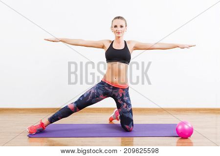 Fit Girl Doing Physical Exercises On Mat At Gym