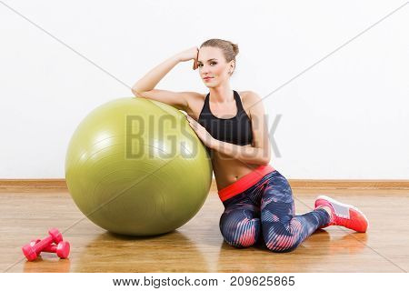 Beautiful Girl Sitting With Fitball At Gym