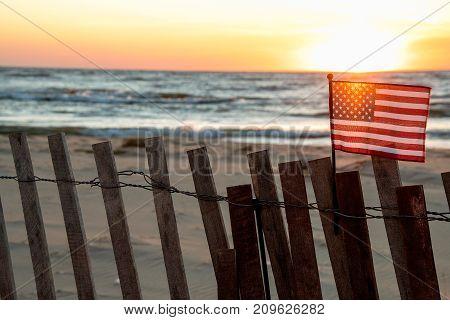 beach fence and sunset illuminating American flag at Lake Michigan
