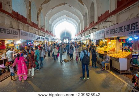 DELHI, INDIA - SEPTEMBER 25 2017: Crowd of people walking and buying inside the Bazaar in the Red Fort in Delhi, India. Meena Bazaar, built by Mukarmat Khan 300 years ago, was the first covered bazaar in India.