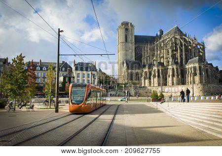 LE MANS FRANCE - OCTOBER 08 2017: Roman cathedral of Saint Julien with an orange tram at a Le mans Sarthe Pays de la Loire France