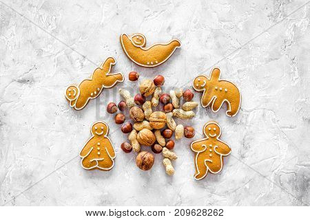 Healthy food for sportsman. Cookies in shape of yoga asanas near nuts on stone table background top view mockup