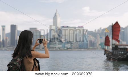 Woman taking photo on Victoria harbor in Hong Kong