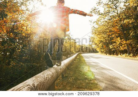 boy walking along the road fence. child keeps balance on the log. copy space for your text