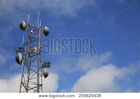 tower of mobile communication. silhouettes of people in a ski lift on a mountain