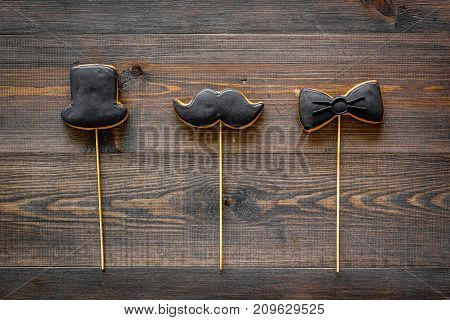 Father's day or birthday celebration with black tie, mustache and hat sign cookies on dark wooden desk background flat lay copyspace