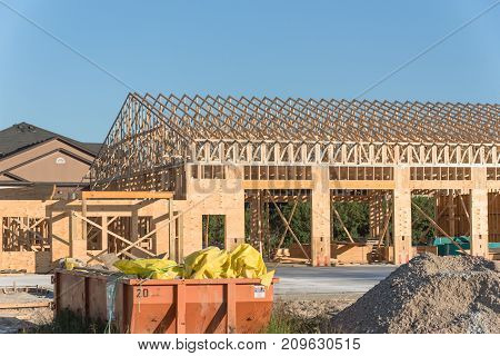 Wood frame house under construction with foundation in Humble Texas USA. New stick built framing one floor commercial building clear blue sky. Industrial dumpster pile of beams logs sand gravel