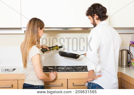Couple trying to cook something in their kitchen