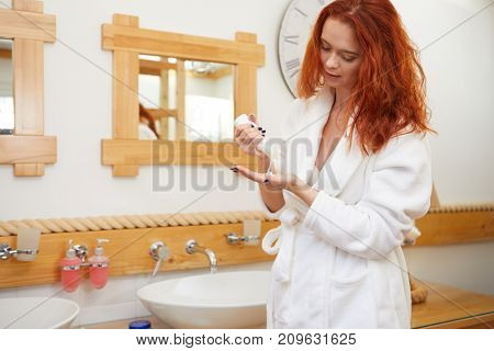 Body care series Beautiful young woman applying cream in the bathroom