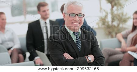 Portrait of happy businessman with  colleagues interacting on background