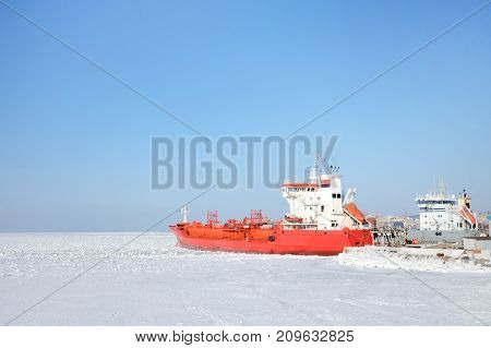 Red expedition ship in the ice at the pier