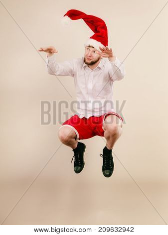 Active young man dancing and jumping in studio on beige. Handsome man in santa claus hat having fun. Christmas xmas season.