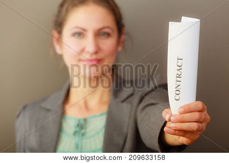 Contracts and agreements concept. Adult beauty woman in jacket holding showing contract. Close up portrait of person with agreement.