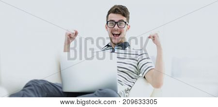 Happy young man using his laptop in bright living room.