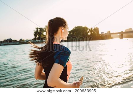 girl in sports clothes listening to music on a run at sunset