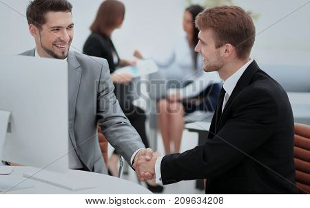 Two happy young men shaking hands while sitting at the office