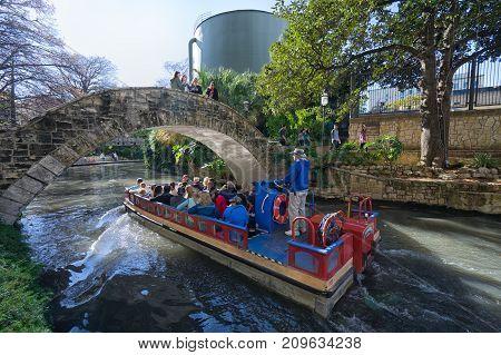 January 3, 2016 San Antonio Texas: tourists enjoying a ride on the San Antonio river on one of the many river cruises crossing under a bridge