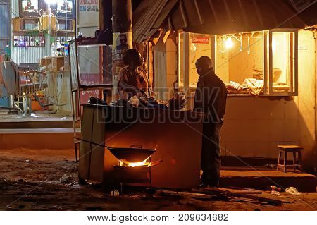 WAKISO UGANDA - SEPTEMBER 3 2017: A street vendor prepares food after nightfall in Wakiso District located in the Central Region of Uganda Africa.