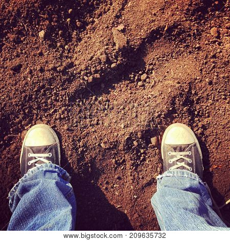 a person wearing sneakers standing on dirt.