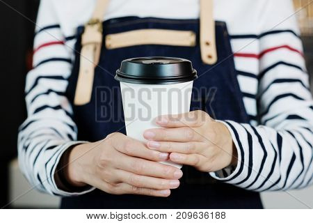 Barista hands holding a take away coffee cup with at cafe counter background small business owner food and drink industry concept