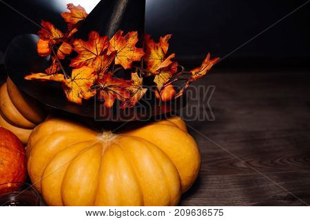 a composition for decorating a house for halloween lie yellow and orange pumpkins, a big black witch hat