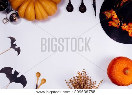 a composition for decorating a house for halloween, on a white table lie yellow and orange pumpkins, a black witch hat decorated with yellow leaves and wooden spoons