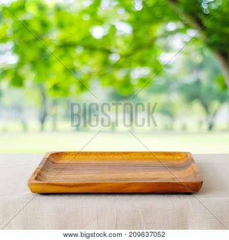Empty wooden tray on sack tablecloth over blur green park background food display montage food background