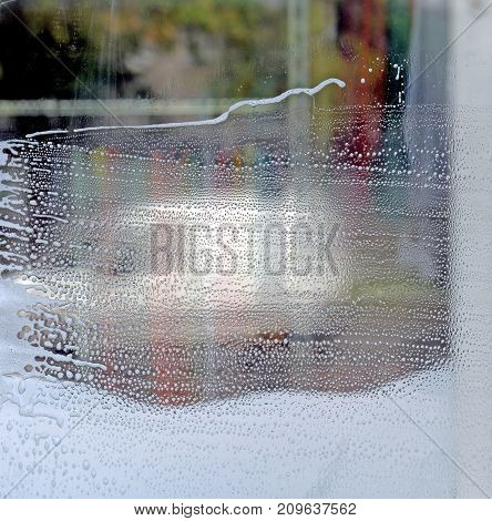 Surface of window or show-window in soapsuds during washing. It is a lot of bubbles of the different size against of different color. Background. Texture.