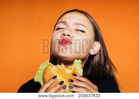 The girl greedily eats a burger. tasty food, isolated on orange background