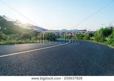 empty highway with an industrial port on background,china.