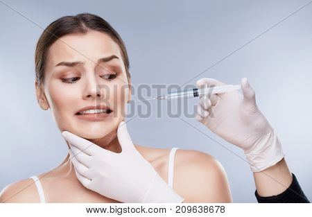 Patient Of Dentist Looking At Syringe In Hands