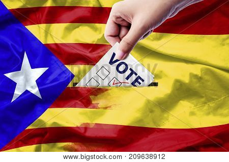 Vote referendum for Catalonia independence exit national crisis separatism risk : close up hand of a person casting a ballot at elections during voting on canvas Spain and Catalan flag background.
