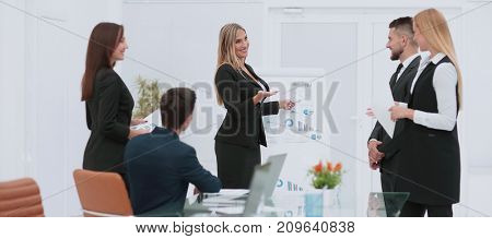 Colleagues asking a question to a businesswoman during a present